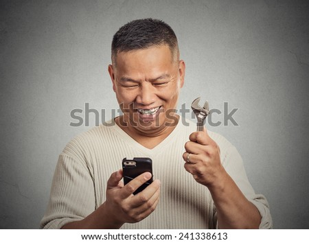 Business solution tools concept. Man looking at smartphone holding wrench key instrument  isolated grey office background. Positive face expression emotion. Success leadership determination - stock photo