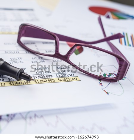 business spreadsheet and eye glass - stock photo