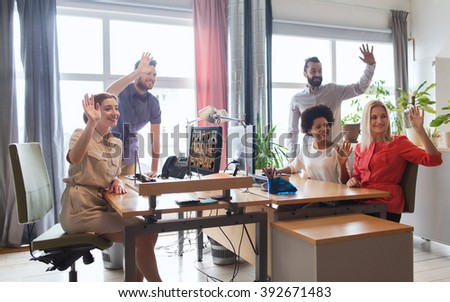 business, startup and office concept - happy creative team waving hands in office - stock photo