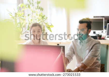 business, startup and people concept - happy creative team networking with computer in office, shot through window glass - stock photo