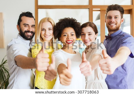 business, startup, people and teamwork concept - happy creative team showing thumbs up in office - stock photo