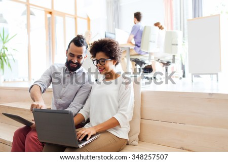 business, startup, technology and people concept - happy international creative team with laptop and tablet pc computer at office - stock photo