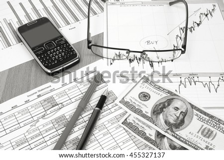 Business still life composition. Financial analysis - income statement, ink pen and US dollars money. Black and white retro style. - stock photo