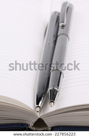 Business still-life diary, two shiny pen; focus on pen tip - stock photo