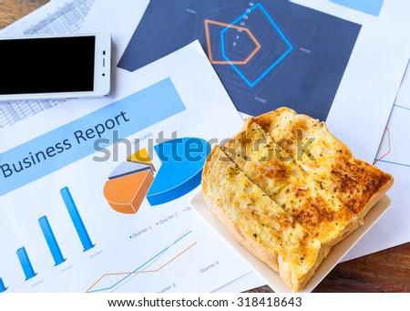 Business still-life of charts, calculator, breakfast - stock photo