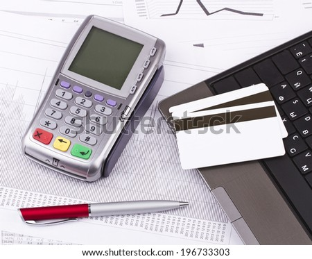 Business still-life of tables, payment terminal, credit Cards, notebook, pen - stock photo