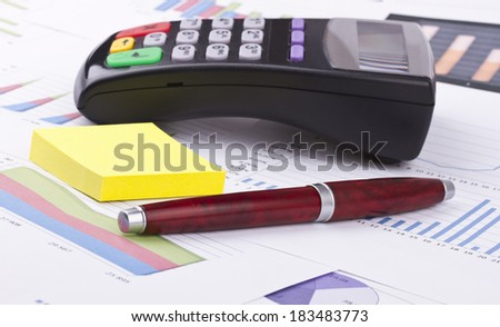 Business still-life of tables, payment terminal, stickers, pen - stock photo