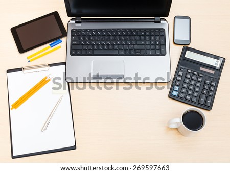 business still life - top view of laptop, tablet PC, smartphone, clipboard, financial calculator, mug of coffee, pen and pencil on office table - stock photo