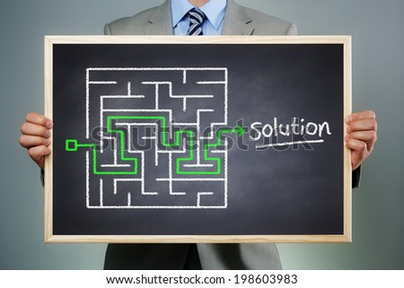 Business strategy businessman holding a blackboard planning and finding a solution through a chalk drawing of a maze - stock photo