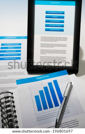Business strategy documents in print and onscreen via mobile device. - stock photo