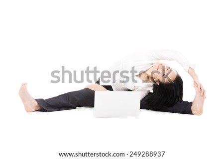 Business, study, healthy lifestyle. Smiling young female office employee doing splits, sitting in yoga pose Parsva Upavishtha Konasana (Upright Seated Angle, Balancing Bear pose) in front of laptop - stock photo