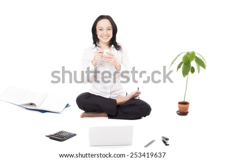 Business, study, healthy lifestyle, work at home. Smiling young woman in formalwear surrounded by office items, drinking coffee, sitting in yoga Padmasana (Lotus Pose) in front of silver laptop - stock photo
