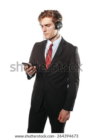 Business-style young handsome guy in headphones with smartphone. Isolated on white. - stock photo