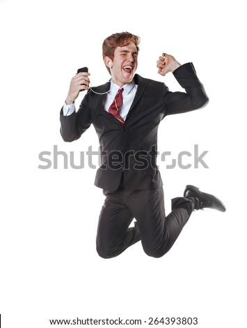 Business-style young handsome guy jumping, enjoying music from his gadget. Isolated on white. - stock photo
