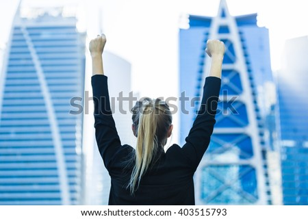 Business success - Celebrating businesswoman overlooking the city center high-rises. - stock photo
