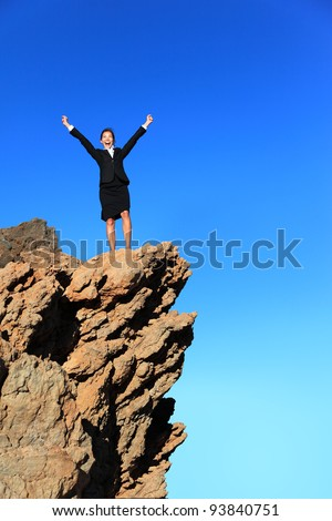 Business success concept. Businesswoman on top of mountain winning overcoming adversity and challenges. Successful young multiracial business woman in suit outdoors in nature. - stock photo