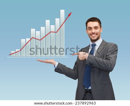 business, success, economics, and people concept - smiling young businessman pointing finger and showing growth chart on palm of his hand over blue background - stock photo