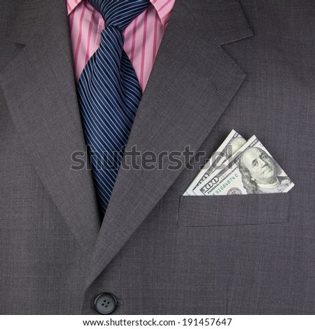 Business suit and dollar in a pocket - stock photo