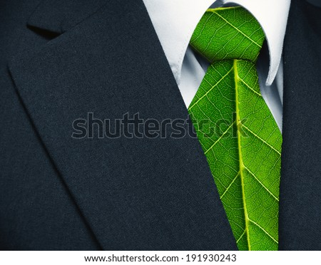 Business suit and green leaves as tie representing a natural job in defense of a green environment. - stock photo