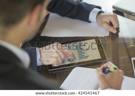 Business table. The finger of a young man pointing at the screen of a tablet with information displayed in graph form. His coworker is taking notes in a notebook. All screen graphics are made up. - stock photo