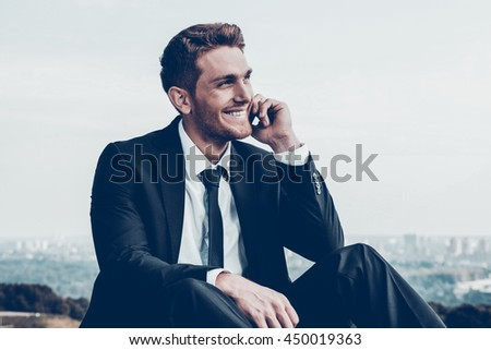 Business talk. Confident young man in formalwear talking on the mobile phone and smiling while sitting outdoors with cityscape in the background - stock photo