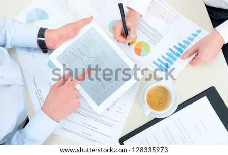 Business team analyzing income charts and graphs with modern digital tablet. Top view photo shoot. - stock photo
