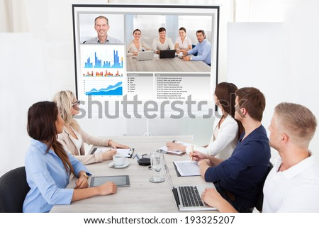 Business team attending video conference at desk in office - stock photo