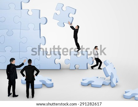 Business team building puzzle pieces together - stock photo
