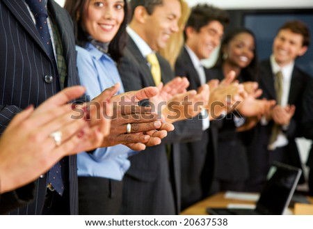 business team clapping in an office facing the camera - stock photo