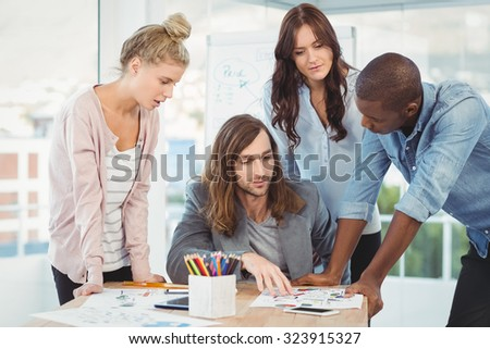 Business team discussing at desk in creative office - stock photo