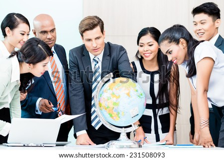 Business team discussing available market intelligence for outsourcing plans looking at globe, Indian, Caucasian, Chinese and Indonesian people - stock photo