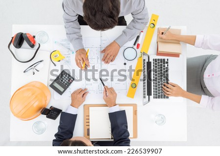 Business team discussing blueprint of the house, view from the top - stock photo