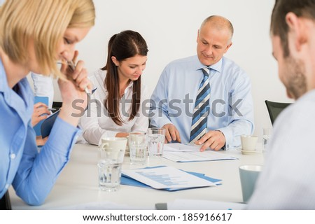 Business team discussing document in boardroom meeting - stock photo