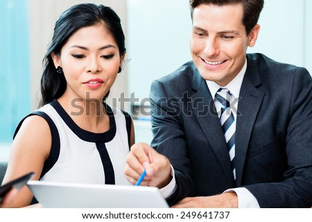 Business team discussing project looking at laptop, mix of Asian and Caucasian people - stock photo