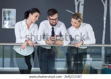 Business team discussing work related matters, standing in an modern office building hall - stock photo