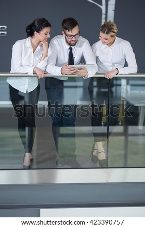 Business team discussing work related matters, standing in an modern office building hall, holding a tablet computer - stock photo