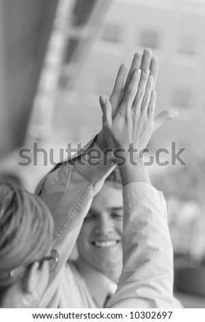 Business team dressed in tan clothes give each other a high five accomplishment - stock photo