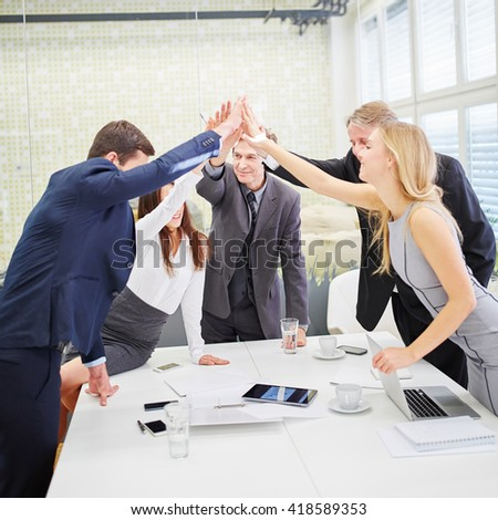 Business team giving each other a high five as motivation in conference room - stock photo