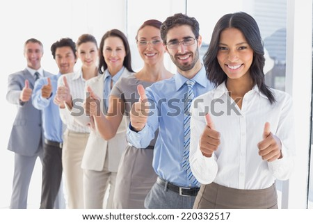 Business team giving thumbs up while smiling at work - stock photo