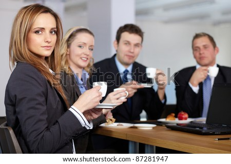 Business team having a coffee break during their meeting, all hold small coffee cups - stock photo