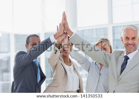 Business team high fiving and smiling at camera in the office - stock photo