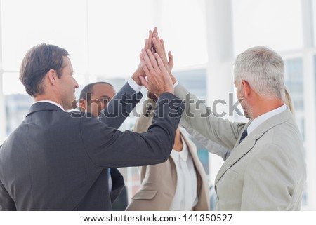 Business team high fiving in a circle in the office - stock photo