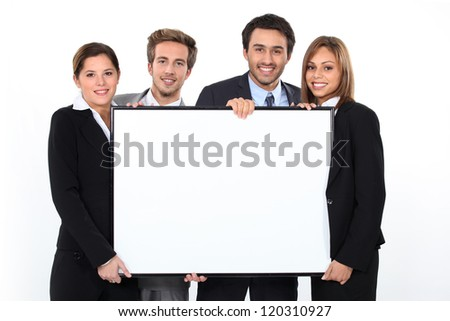 Business team holding blank poster - stock photo