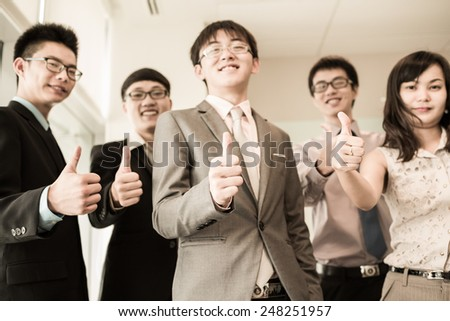 Business team holding their thumbs up.Asian - stock photo