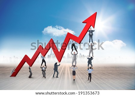 Business team holding up arrow against cityscape on the horizon - stock photo