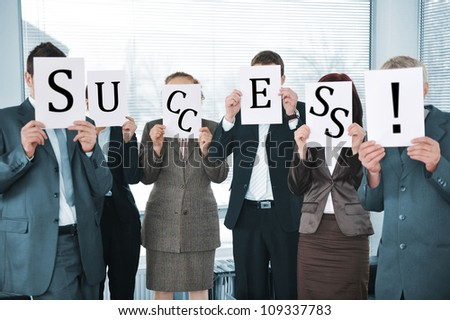 Business team holding white papers in office - stock photo