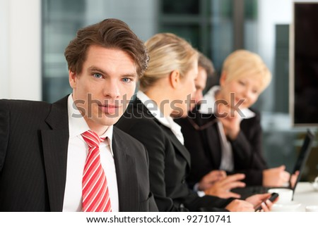 Business - team in an office; a young colleague is looking into the camera - stock photo