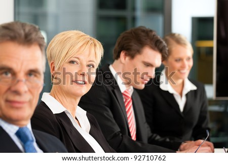 Business - team in an office; the boss is looking into the camera - stock photo