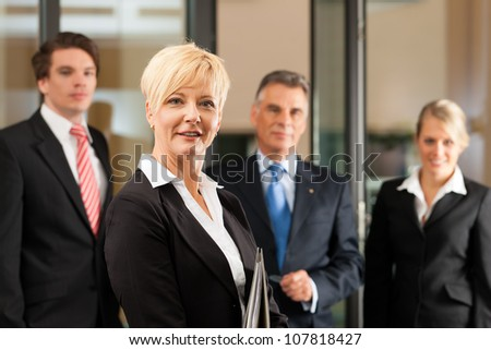 Business - team in an office, the female manager is standing in front - stock photo