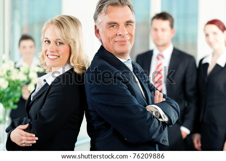 Business - team in an office; the senior executive is standing in front with his secretary - stock photo